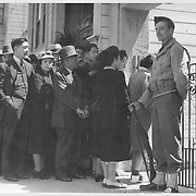 Japanese family heads and persons living alone form a line outside Civil Control station located in the Japanese American Citizens League Auditorium at 2031 Bush Street, to appear for processing in response to Civilian Exclusion Order No. 20. -- Photographer: Lange, Dorothea -- San Francisco, California. 4/25/42<br /> Identifier:<br /> Volume 57<br /> Identifier:<br /> Section G<br /> Identifier:<br /> WRA no. A-531<br /> Collection:<br /> War Relocation Authority Photographs of Japanese-American Evacuation and Resettlement Series 14: Preevacuation<br /> Contributing Institution:<br /> The Bancroft Library. University of California, Berkeley.