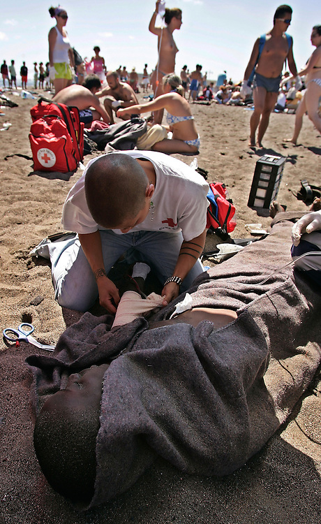 An immigrant is helped by a red cross worker after a small boat, seen in background, of would-be immigrants landed on the Tejita beach in Granadilla on the Canary island of Tenerife, Spain, Sunday, July 30, 2006. More than 117 would-be immigrants arrived in different boats Sunday in Tenerife, two of whom were found dead. More than 11,000 Africans from some of the continent's poorest countries have made the perilous trip to the Canary Islands from western coasts so far this year, already doubling the total for all of 2005. More than 1,000 are reported to have died attempting the voyage since late last year.