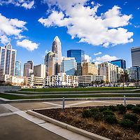 Charlotte skyline at Romare Bearden Park with downtown Charlotte city buildings against a blue sky with clouds. Includes One Wells Fargo Center, Two Wells Fargo Center, Bank of America Corporate Center, Bank of America Plaza, 121 West Trade building, and Carillon Tower. Charlotte, North Carolina is a major city in the Eastern United States of America