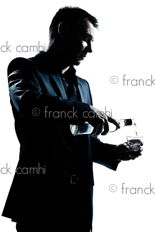 one caucasian man portrait pouring white alcohol silhouette in studio isolated white background