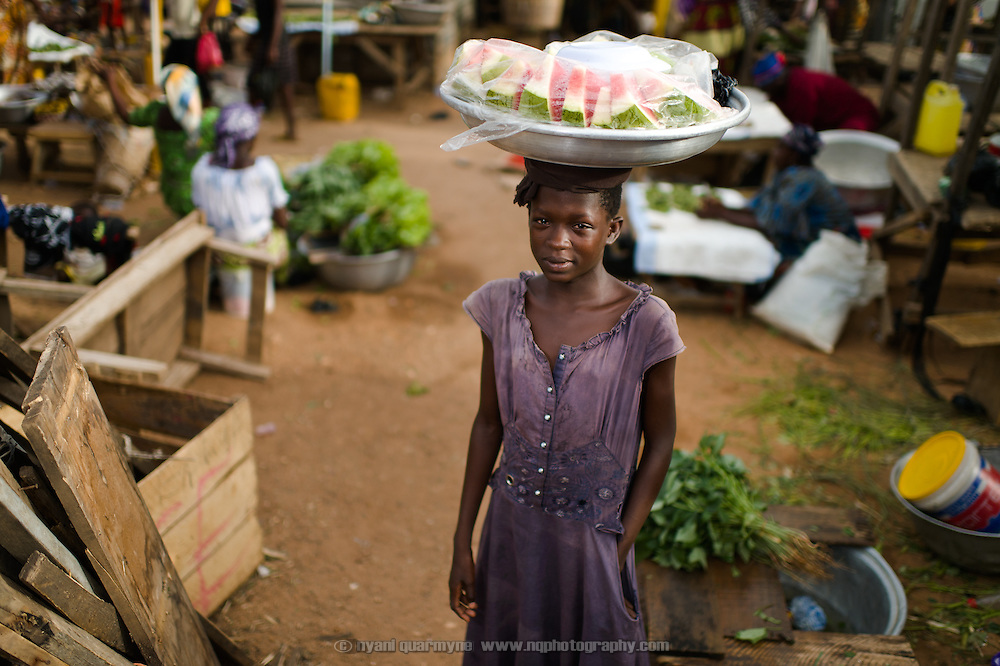 Jenet Naa, pictured in a market in the Upper West region of Ghana on 28 May 2014, explained through tears that she was selling watermelon in the marketplace to earn enough money to buy a new school uniform—she had damaged hers beyond repair, catching it on a nail sticking up from a piece of furniture. With the day mostly over, she indicated that she had sold GHS 16.00 (£3.15)  worth of watermelon slices thus far, for which she expected to be paid GHS 2.00  (£0.40) by the owner of the fruit. Approximately 12 years old and in 4th grade at school, she estimates that she needs about GHS 19.00  (£3.75) for a new uniform. She says her parents cannot afford to buy it for her. Without a uniform, she will not be allowed to attend school.