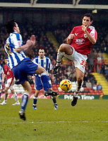 Photo: Leigh Quinnell.<br /> Bristol City v Huddersfield Town. Coca Cola League 1. 10/02/2007. Bristol Citys Lee Johnson jumps into a challenge with Huddersfields Michael Collins.