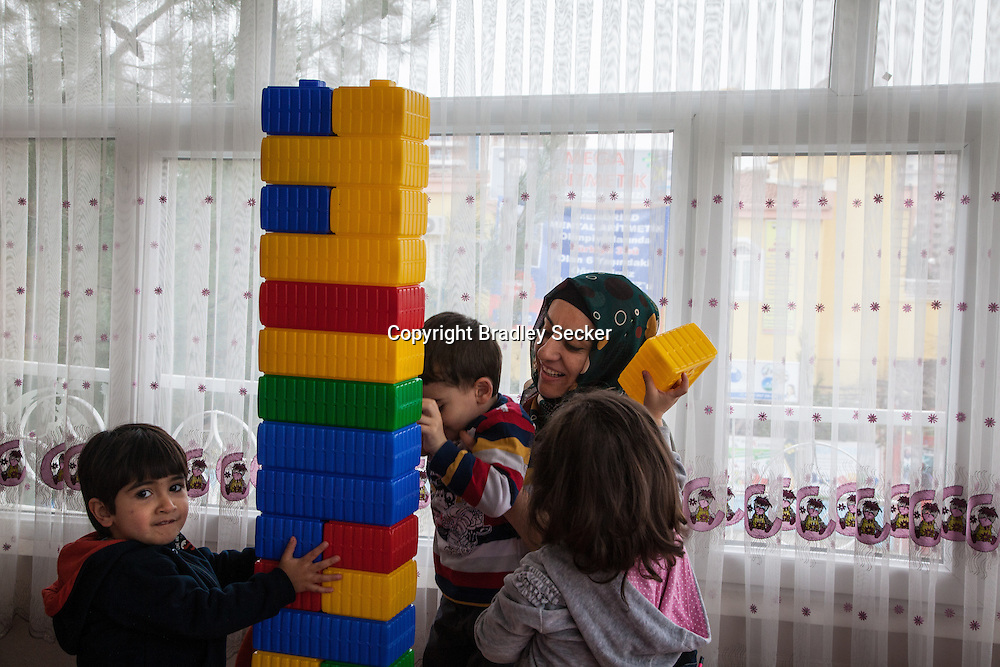 DIYARBAKIR, TURKEY. FEBRUARY 22, 2013 Teacher Gulistan Akbas, centre, playing with young children at a Kurdish language creche in Diyarbakir.