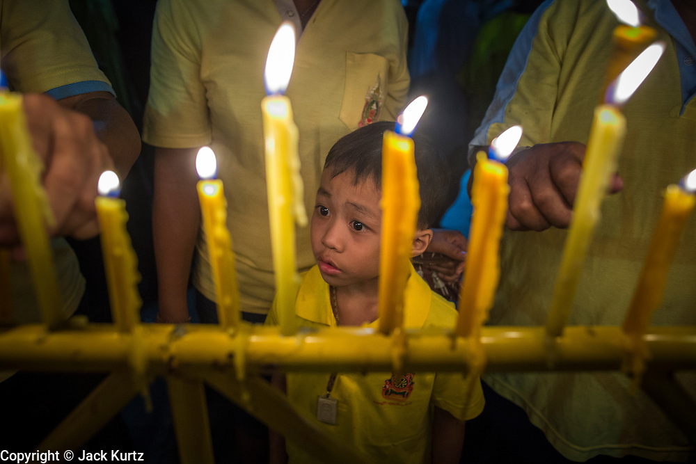05 DECEMBER 2012 - BANGKOK, THAILAND: A boy looks up at candles lit for the King during the public ceremony to celebrate the birthday of Bhumibol Adulyadej, the King of Thailand, on Sanam Luang, a vast public space in front of the Grand Palace in Bangkok Wednesday night. The King celebrated his 85th birthday Wednesday and hundreds of thousands of Thais attended the day long celebration around the Grand Palace and the Royal Plaza, north of the Palace. The Thai monarch is revered by most Thais as unifying force in Thailand's society, which is not yet recovered from the political violence of 2010.      PHOTO BY JACK KURTZ