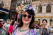 New York, NY - April 16, 2017. A woman wears a floral hat  at New York's annual Easter Bonnet Parade and Festival on Fifth Avenue.