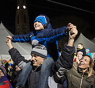 Goshen, New York - Ryan Schramm, 9, of Goshen watches the raising of the illuminated sulky from the shoulders of his father Tim during the Illuminate Goshen New Year's Eve Ball Drop on Dec. 31, 2016. Ryan's mother Tracy Schramm is at right.