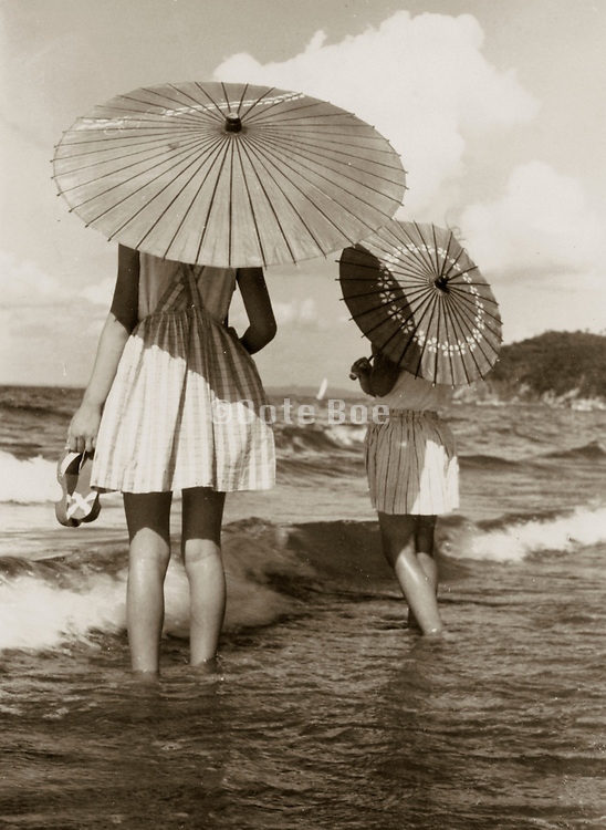 Two girls walking in the surf.