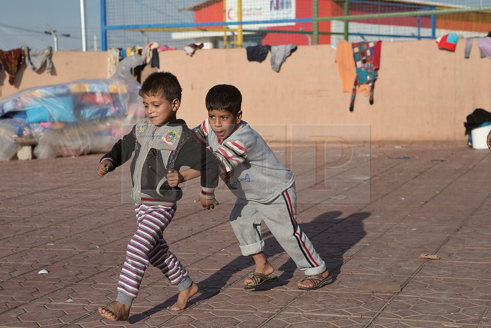 Licensed to London News Pictures. 22/10/2016. Two young Iraqi refugee boys, newly arrived from areas where the Mosul Offensive is taking place, play in the court yard of a school at the Dibaga refugee camp near Makhmur, Iraq. Upon arriving at the camp women and children stay in the school for around 10 - 15 days whilst completing the registration process.<br /> <br /> The crowded Dibaga camp, housing around 28,000 Sunni Arab refugees, is the main gathering point for new IDPs now fleeing areas where ISIS have been pushed out or are in conflict with the Iraqi Army. Photo credit: Matt Cetti-Roberts/LNP