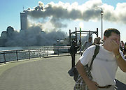 People escaping New York by ferry arrive at the New York Waterway dock on the  Jersey City waterfront after one of the World Trade Towers collapsed.