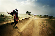 Tanzania, traditional Maasai life. Matayo walks on the main road leading out of Loiborsoit as a dust cloud blows by.