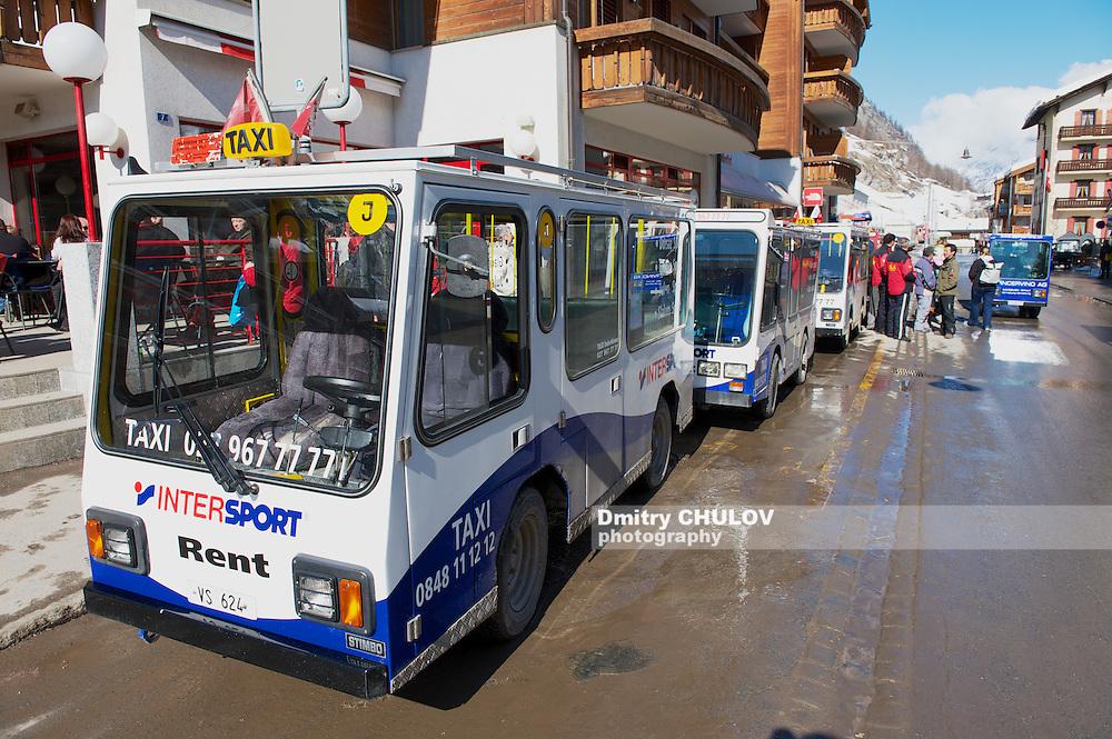 ZERMATT, SWITZERLAND - MARCH 03, 2009: Electro taxis wait for passengers in Zermatt, Switzerland. To prevent air pollution the entire town of Zermatt is a combustion-engine car-free zone.