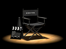 Director's chair with megaphone and clapper board on a wood floor under a spotlight