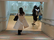 A stairwell in a department store with women descending the stairs
