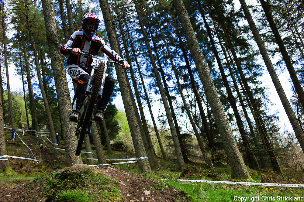 Ae Forest, Dumfries, Scotland, UK. 25th April 2015. Samuel Rodda of Highland Bikes Racing springs off a tree stump at the 7Stanes course in Ae Forest during the Scottish Downhill Association racing.
