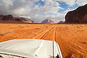 A jeep drives through the desert towards high sandstone cliffs in Wadi Rum, Jordan.