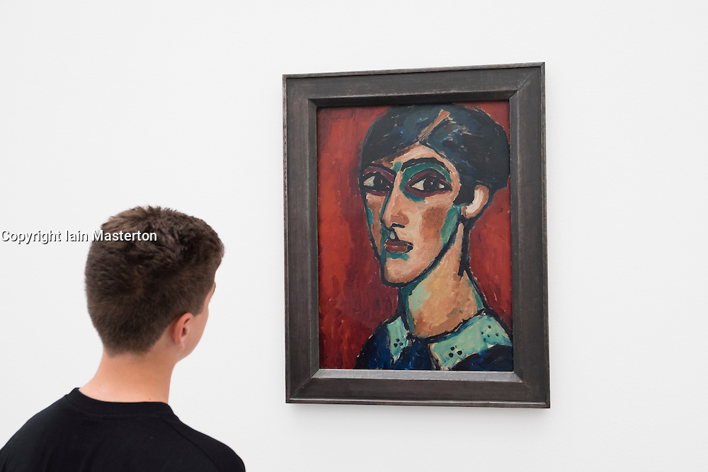 "Boy looking at painting by Alexej von Jawlensky "" Langlicher Kopf in Braunrot"" at Pinakothek Museum in Munich Germany"