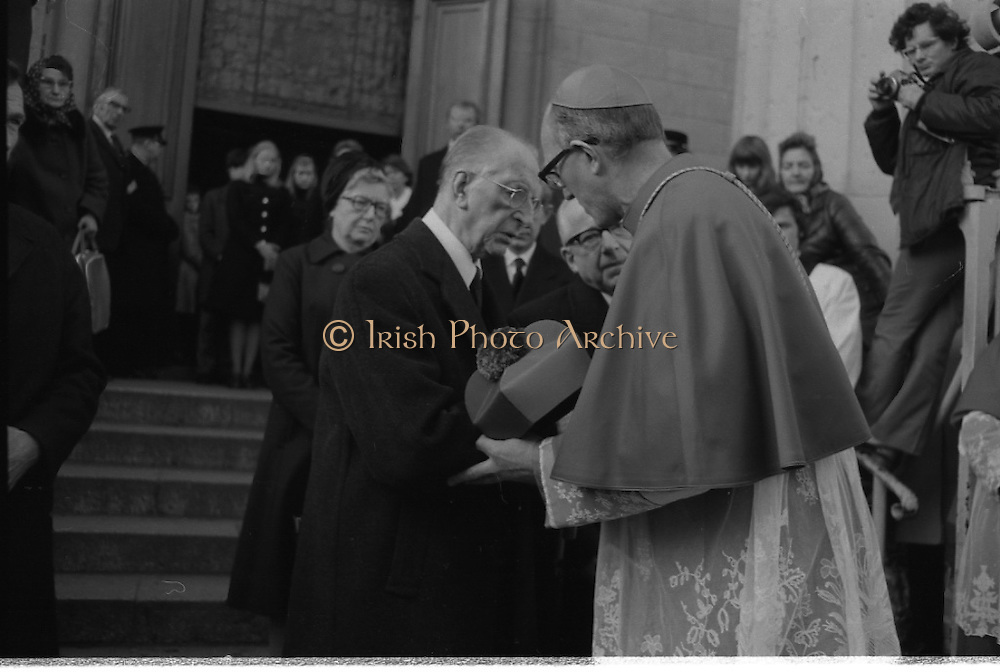 Funeral of Sinead Bean DeValera.    (H82)..1975..09.01.1975..01.09.1975..9th January 1975..Today saw the funeral of Sinead Bean DeValera take place at the Pro Cathedral, Dublin. She was the wife of Ex-President Eamon DeValera. Mrs Devalera was a noted author of childrens literature..Mrs DeValera, Born 3rd June 1878. Died 7th Jan 1975...Picture of Eamon DeValera being consoled by the Archbishop of Dublin,Dr Ryan on the death of his wife Sinead.