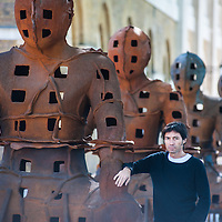 London, UK - 2 September 2014: Artist Xavier Mascaró poses next to his installation 'Guardians'. These rusted iron warriors, nearly 10 feet high, are both imposing and placid, and are inspired by medieval armour and ancient Egyptian and Greek art. Xavier Mascaró's first UK solo exhibition will run from 3 September until 5 October at Saatchi Gallery.