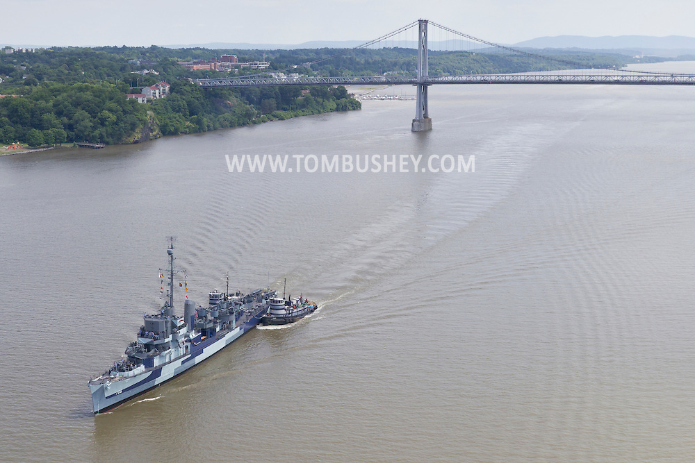 Highland, New York - The USS Slater approaches the Walkway over the Hudson on its way north on the Hudson River on June 30, 2014. The Slater served in World War II and is the last destroyer escort vessel afloat in America. The Slater was on the way to Albany, N.Y., to resume its duties as a floating museum. The Mid-Hudson Bridge is in the background. The tugboats Frances, right, and Margot, assisted the Slater.
