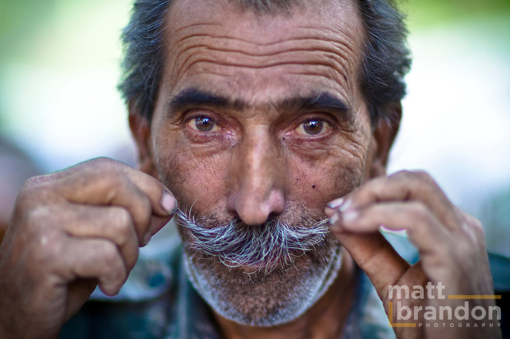 A Dha Hanu man lifts his mustache up for the camera.