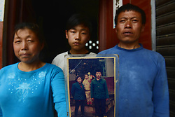 59601374  .The Luo family pose for photo with an old picture in the quake-hit Longmen Village, southwest China s Sichuan Province, May 4, 2013. The old picture of the Luo couple and their daughter was taken in 1997 when their son hadn t been born. Old photos are not daily necessities for who just suffered a 7-magnitude earthquake, but they are still cherished as they recorded peoples past life and recalled memories, May 4, 2013.  Photo by: i-Images.UK ONLY