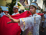 18 NOVEMBER 2015 - BANGKOK, THAILAND:  Men in traditional Brahmin's priest outfits carry a red cloth inscribed with prayers during the Wat Saket temple fair parade marking the start of the temple's annual fair. Wat Saket is on a man-made hill in the historic section of Bangkok. The temple has golden spire that is 260 feet high which was the highest point in Bangkok for more than 100 years. The temple construction began in the 1800s in the reign of King Rama III and was completed in the reign of King Rama IV. The annual temple fair is held on the 12th lunar month, for nine days around the November full moon. During the fair a red cloth (reminiscent of a monk's robe) is placed around the Golden Mount while the temple grounds hosts Thai traditional theatre, food stalls and traditional shows.     PHOTO BY JACK KURTZ