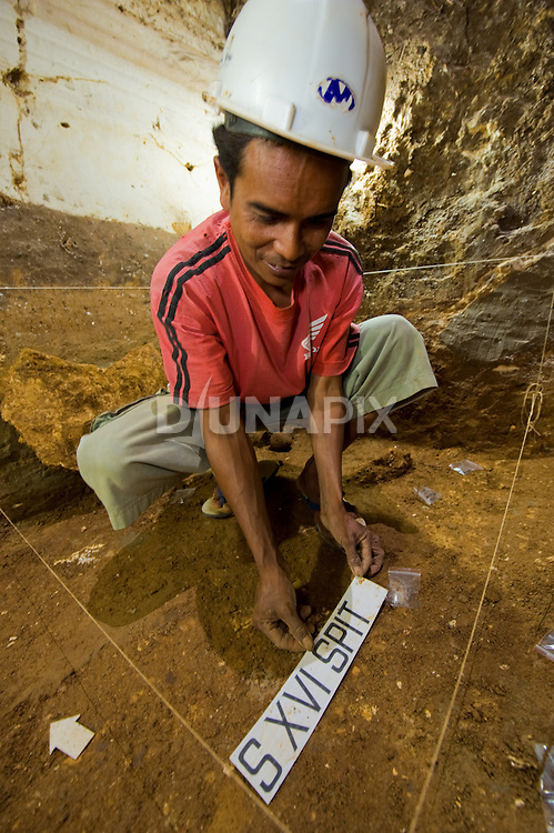 """A Manggarai excavator prepares a spit for photodocumentation inside an excavation pit at Liang Bua cave,  discovery site of the Flores """"hobbit"""", Homo floresiensis."""