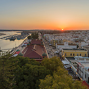 Aerial sunset cityscape of Olhao downtown, Algarve fishing village view of ancient neighbourhoods traditional cubist architecture and landmark market. Portugal.