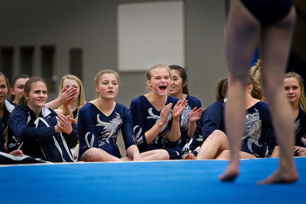 Champlin Park captain Amanda Cunningham, center right, cheers on a teammate during the dual gymnastics meet against Coon Rapids High School at Champlin Park, Friday, January 31, 2014. Champlin Park won the meet with a combined score of 137.35 over Coon Rapids' 125.975.