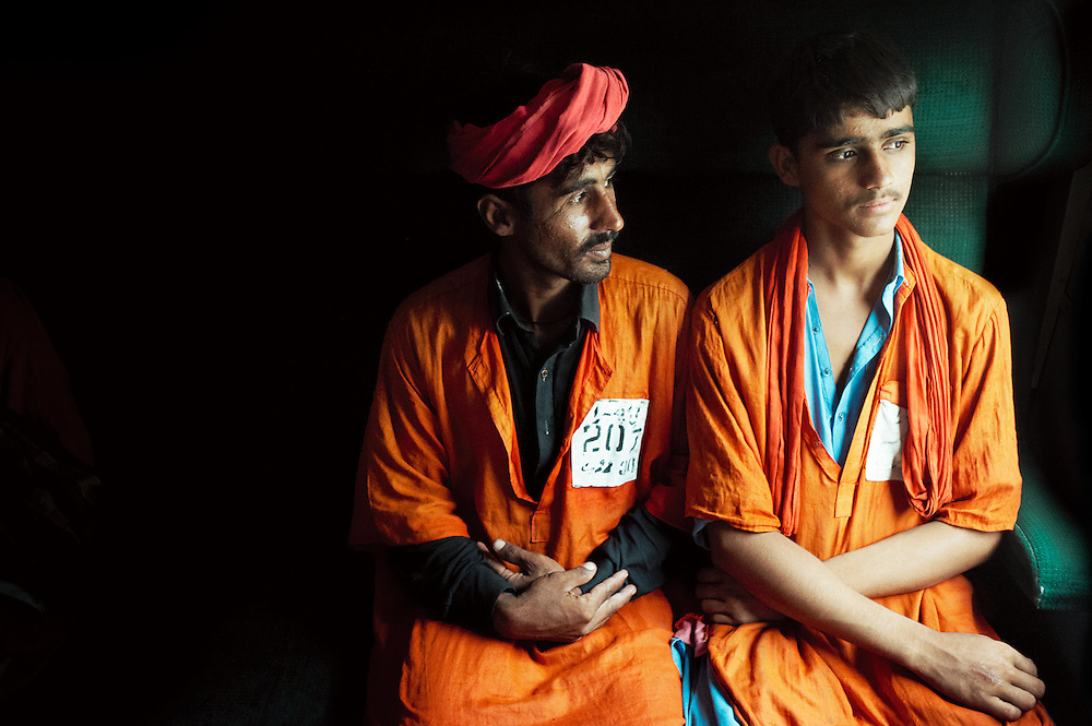 Porters Porter Muhammad Lodara, 70 years old, Muhammad Zamir Hussain, 18 years old and Porter Munir Ahmed, 26 years old sit on the Khyber Mail traveling from Rawalpindi to Karachi on August 13, 2011.
