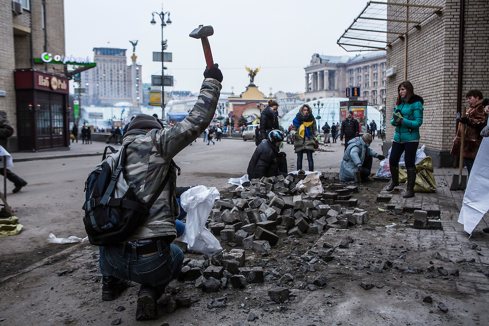 KIEV, UKRAINE - FEBRUARY 19: An anti-government protester breaks up cobblestones to be used as ammunition against police on Independence Square on February 19, 2014 in Kiev, Ukraine. After several weeks of calm, violence has again flared between anti-government protesters and police as the Ukrainian parliament is meant to take up the question of whether to revert to the country's 2004 constitution. (Photo by Brendan Hoffman/Getty Images) *** Local Caption ***