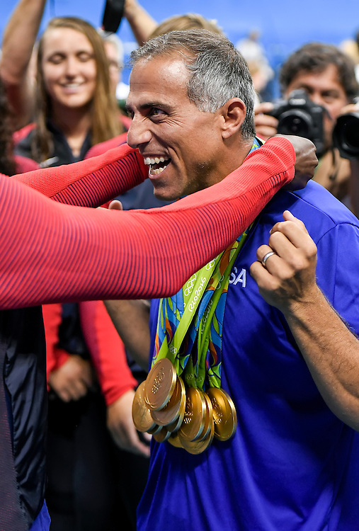Wearing the gold medals from the entire USA women's water polo team, head coach Adam Krikorian laughed as the last gold medal was placed around his neck by goalkeeper Ashleigh Johnson following the team's 12-5 win over Italy on Friday at Olympic Aquatics Stadium during the 2016 Summer Olympics Games in Rio de Janeiro, Brazil.