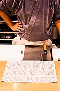Chef Nakamura with dinner menu at Nakamura restaurant.