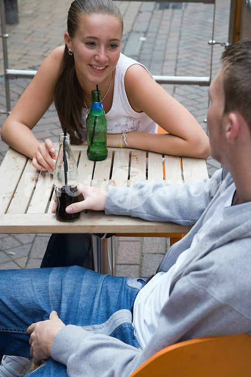 Two teenagers enjoying a drink together,