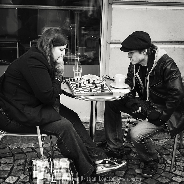 Young couple sitting outside a cafe in central Bergen Norway playing chess while having coffee