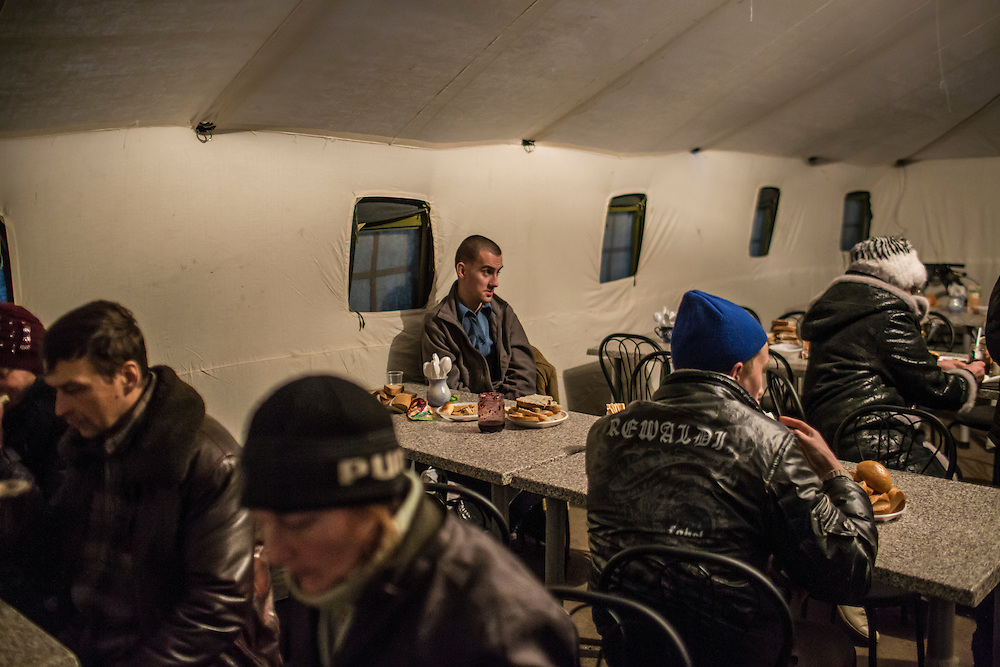 SLOVYANSK, UKRAINE - FEBRUARY 7, 2015: People displaced by fighting in the town of Debaltseve gather in a tent where they can receive a hot meal at the train station in Slovyansk, Ukraine. Many civilians have been evacuated from Debaltseve and brought to Slovyansk, where they are either given a free onward ticket or housed in a train until they can make further plans. CREDIT: Brendan Hoffman for The New York Times