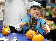 Middletown, New York - A young boy wearing a costume decorates a pumpkin at the Family Fall Festival at the Middletown YMCA on Oct. 23, 2010.
