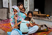Nafeesa, 27, poses for a portrait with her 4 children aged 10, 7, 4, and 1and a half years, in her house compound in a slum in Tonk, Rajasthan, India, on 19th June 2012. Nafeesa's health deteriorated from bad birth spacing and over-working. While her husband works far from home, she rolls bidis (indian cigarettes) to make an income and support the family. She single-handedly runs the household and this has taken a toll on her health and financial insufficiencies has affected her children's health. Photo by Suzanne Lee for Save The Children UK