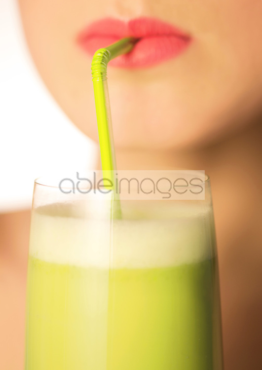 Close up of a woman mouth drinking a vegetable smoothie with a straw