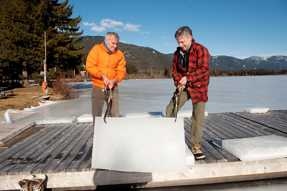 Men harvest ice blocks from a frozen lake with a chainsaw to harvest blocks for an ice carving contest.  Whistler BC, Canada