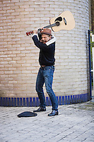 Aggressive young man breaking guitar against brick wall on street