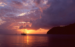 Silhouette of sailboat on water at sunset in the Caribbean.