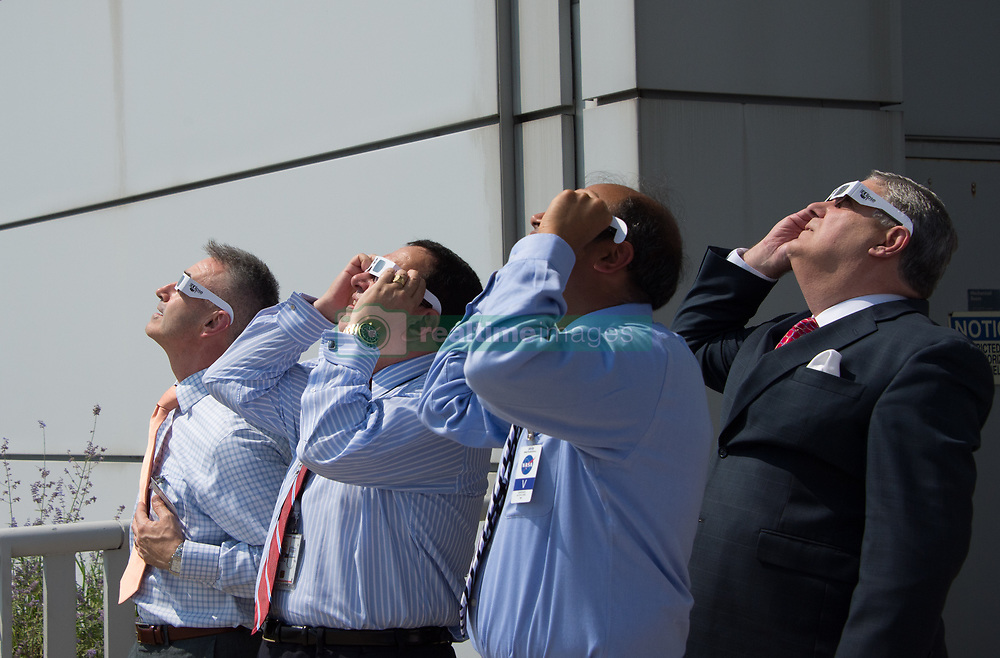 NASA employees and vistors use protective glasses to view a partial solar eclipse from NASA Headquarters Monday, Aug. 21, 2017 in Washington, DC. A total solar eclipse swept across a narrow portion of the contiguous United States from Lincoln Beach, Oregon to Charleston, South Carolina. A partial solar eclipse was visible across the entire North American continent along with parts of South America, Africa, and Europe.  Photo Credit: (NASA/Connie Moore)