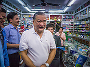 16 JANUARY 2013 - BANGKOK, THAILAND:  SUKHUMBHAND PARIBATRA, candidate for Governor of Bangkok, walks through a pharmacy during a campaign appearance in Bangkok. The Oxford educated Sukhumbhand is a member of the Thai royal family (he is a great grandson of the late Thai King Chulalongkorn). He is a member of the Thai Democrat party and was first elected Governor of Bangkok in 2009. He is running for reelection this year. Sukhumbhand faces six challengers in the March 3 election. His toughest opponent is expected to be Police General Pongsapat Pongcharoen, who is running under the banner of the Pheu Thai Party, which controls the Prime Minister's office and Parliament.    PHOTO BY JACK KURTZ