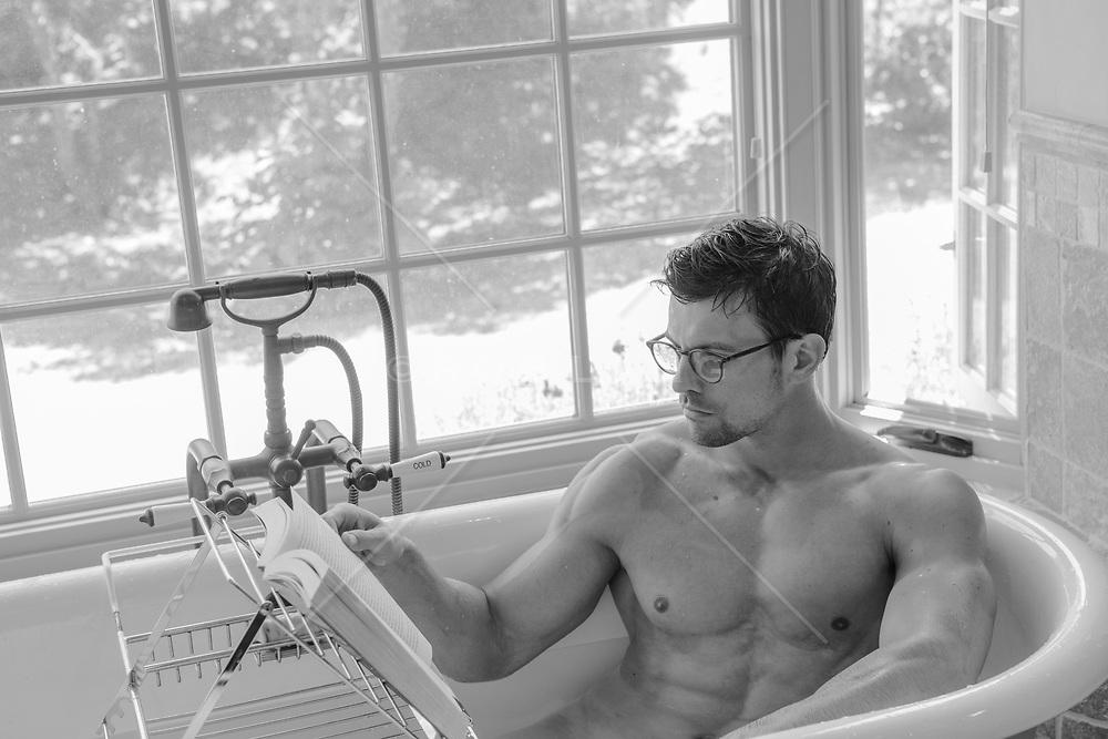hot man in a bathtub reading a book