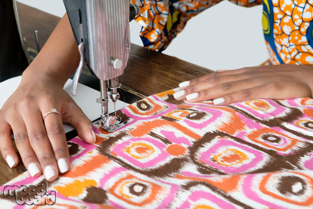 Female tailor stitching patterned cloth on sewing machine