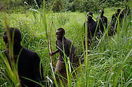 "A boy patrols his community with the local ""arrow boy"" force, to defend against the LRA."