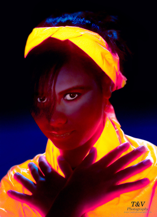 Portrait of a young girl wearing a glowing orange top and headband.Black light