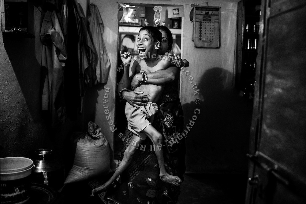 A smiling Suraj Pratap Singh, 18, a boy affected by severe cerebral palsy, is being lifted by his mother, Kaser Bai, 40, a '1984 Gas Survivor', to be washed in front of their home in Chola, one of the water-affected colonies in Bhopal, Madhya Pradesh, central India, near the abandoned Union Carbide (now DOW Chemical) industrial complex.