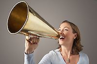 Smiling Mid-adult woman shouting through megaphone